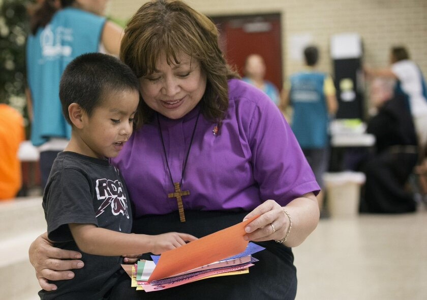 United Methodist Bishop Minerva Carcano (right) shares letters of encouragement with Regino Enrique at the immigrant welcome center at Sacred Heart Catholic Church in McAllen, Texas. The 5-year-old and his mother, Macaria, who did not share their last names, arrived from Guatemala after a month-lon