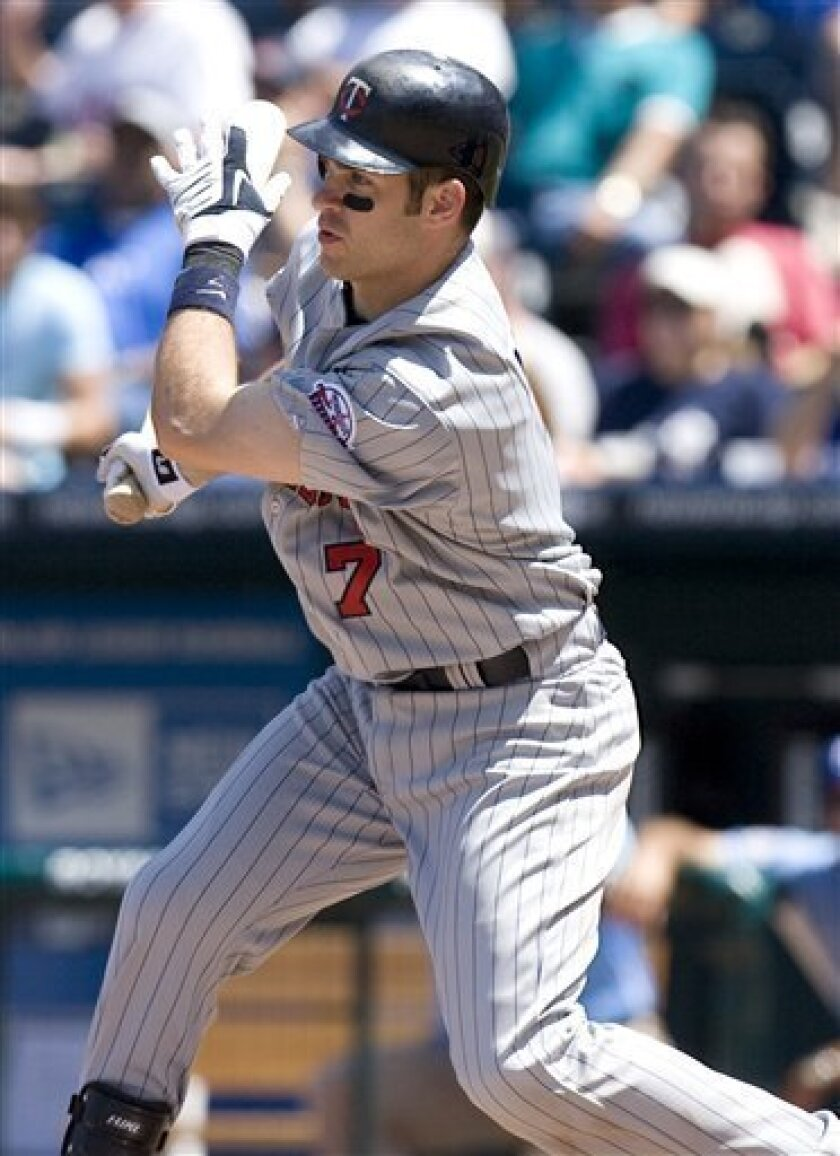 Minnesota Twins' Joe Mauer drives the ball into center for an RBI single in the sixth inning of a baseball game against the Kansas City Royals on Wednesday, July 1, 2009, in Kansas City, Mo. (AP Photo/Ed Zurga)