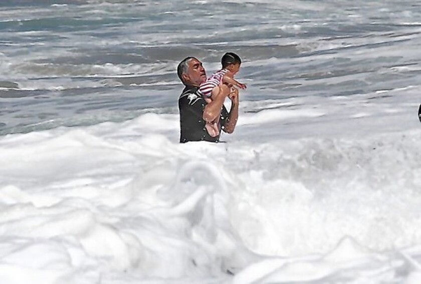 Man rescues baby from rough surf