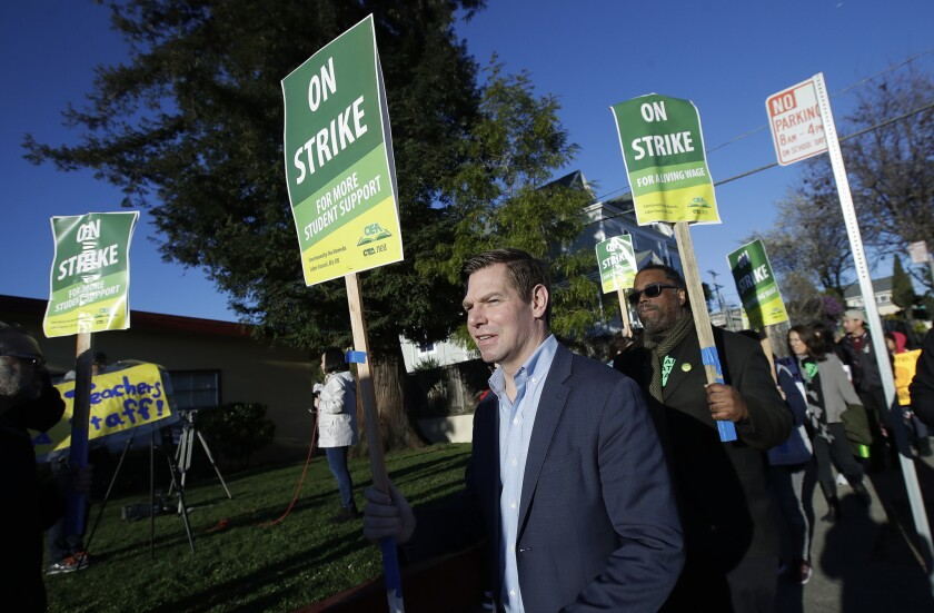 Rep. Eric Swalwell, D-Calif., center, marches along with teachers and supporters outside of Manzanita Community School in Oakland. Teachers in Oakland went on strike Thursday in the country's latest walkout by educators over classroom conditions and pay.