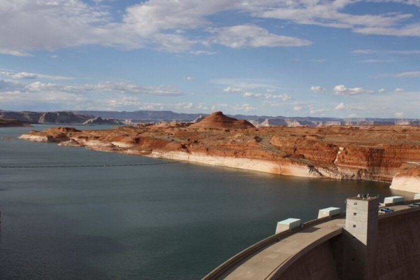 "Lake Powell's ""bathtub ring"" of mineral salts shows the drop in water level caused by an ongoing drought in the Colorado River Basin. In the foreground is Glen Canyon Dam."