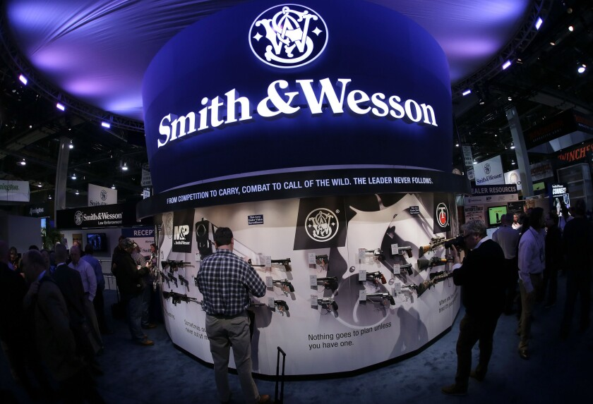 Trade show attendees examine handguns and rifles in the Smith & Wesson display at the Shooting, Hunting and Outdoor Tradeshow in Las Vegas.