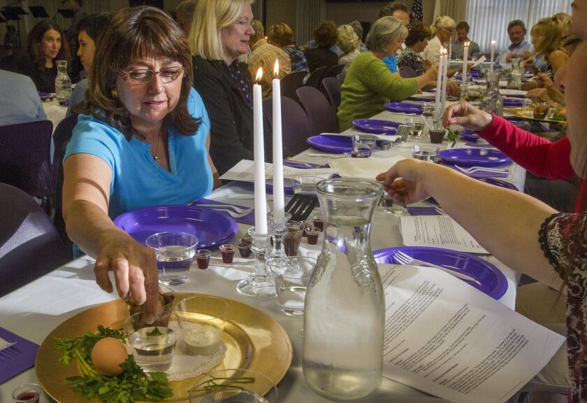 In remembrance of the suffering of Hebrew slaves Colleen Billings, left, dips her green vegetable called Karpas into salt water during a ceremonial Passover dinner at the Christ Presbyterian Church in Carlsbad Thursday. photo by Bill Wechter