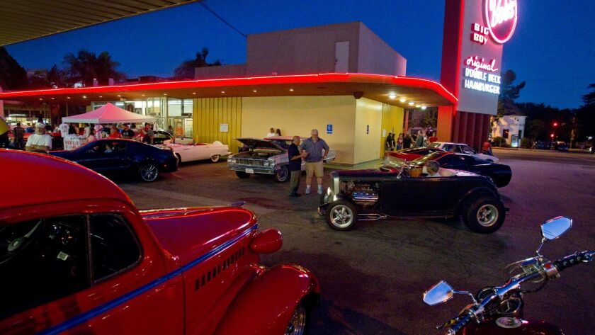 Classic car enthusiasts cruise and show off their cars in the parking lot of Bob's Big Boy restauran