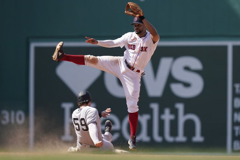 New York Yankees' Luke Voit (59) slides out at second base as Boston Red Sox's Xander Bogaerts follows through on a throw to first to complete a double play in the eighth inning of a baseball game, Sunday, June 27, 2021, in Boston. (AP Photo/Steven Senne)