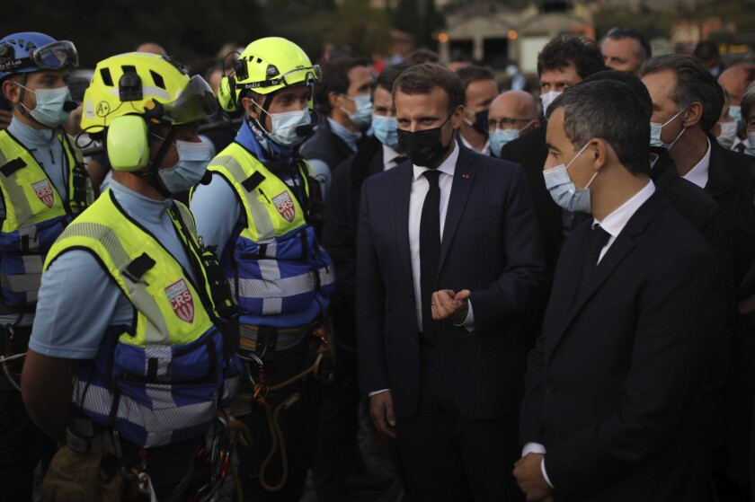 French President Emmanuel Macron, center, gestures towards French Interior Minister Gerald Darmanin, right, as he meets police officers rescuers in Breil-sur-Roya, southeastern France, Wednesday, Oct.7, 2020. With more than a dozen dead and others missing, France and Italy are still assessing damage and cleaning up after violent rains that began Friday, sweeping away homes and unearthing bodies from cemeteries. French President Emmanuel Macron is visiting the mountainous area near the Mediterranean coast Wednesday, and promised government aid to flood victims. (AP Photo/Daniel Cole, Pool)