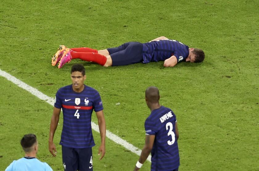 El lateral francés Benjamin Pavard tirado en el piso durante el partido contra Alemania por la Euro 2020, el martes 15 de junio de 2021, en Múnich. (AP Foto/Alexander Hassenstein, Pool)