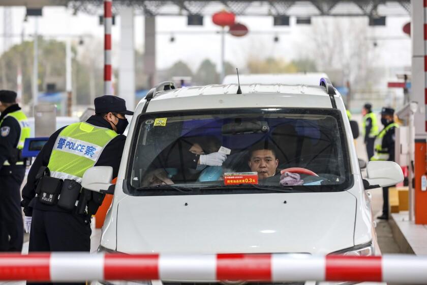 Police in China screen travelers for coronavirus