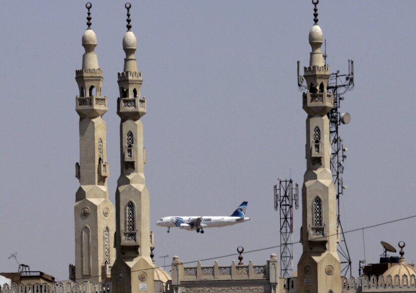 FILE - In this May 21, 2016 file photo, an EgyptAir plane flies past minarets of a mosque as it approaches Cairo International Airport, in Cairo, Egypt. A French company says Wednesday, June 2, 2016 its equipment aboard a French naval ship has detected signals from one of the black box flight recor