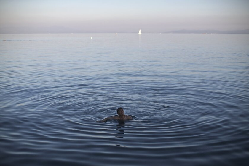 An Afghan man swims in the Aegean sea as he waits for a ferry to transport him to Athens in the port of Mytilene, on the island of Lesbos, Greece, Wednesday, Nov. 4, 2015. Thousands of migrants and refugees are stranded on Lesbos due to a ferry strike that began Monday. (AP Photo/Marko Drobnjakovic