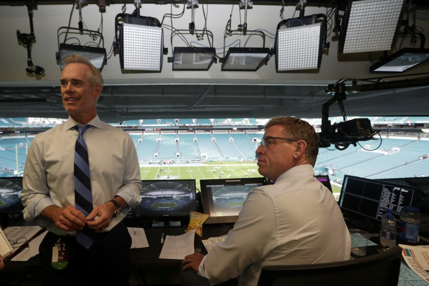 Fox Sports play-by-play announcer Joe Buck, left, and analyst Troy Aikman  work in the broadcast booth