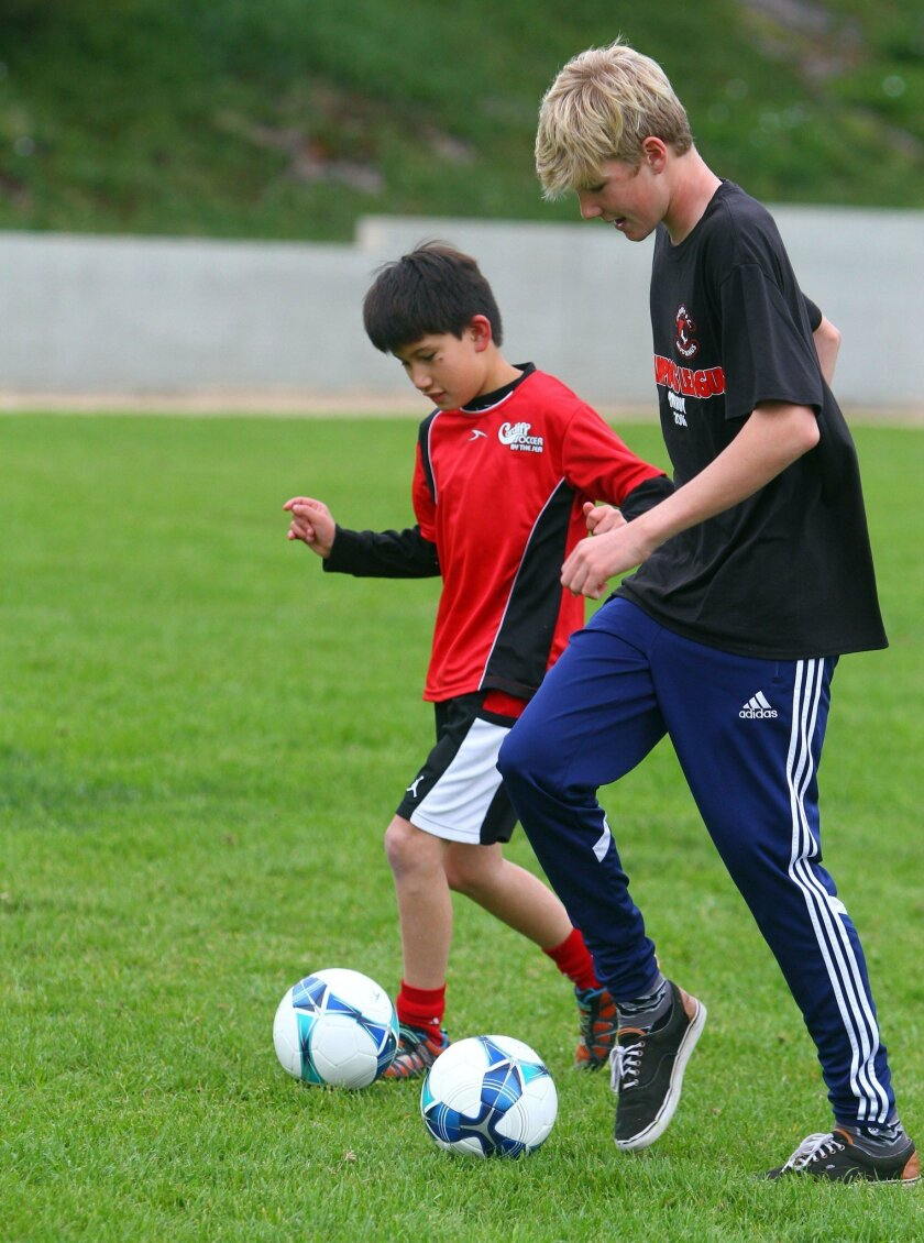 Champions League program buddy Sam Fraser, 14, right, teaches soccer skills to Ryan Watanabe, 9, Saturday at Ada Harris Elementary School in Cardiff. The Champions League is for young players special needs.