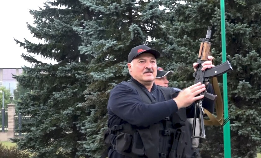 Belarus President Alexander Lukashenko holds a rifle near the Palace of Independence in Minsk, Belarus, on Aug. 23.