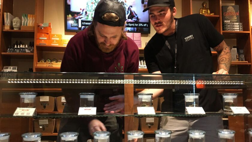 Employees Matt Sullivan, left, and Taron McElroy arrange jars of cannabis at Torrey Holistics in San Diego in 2017.