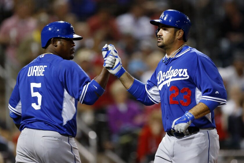 Los Angeles Dodgers' Adrian Gonzalez (23) is congratulated by Juan Uribe (5) after hitting a solo home run against the Cincinnati Reds in the sixth inning during an exhibition baseball game in Goodyear, Ariz., Wednesday, March 5, 2014. (AP Photo/Paul Sancya)
