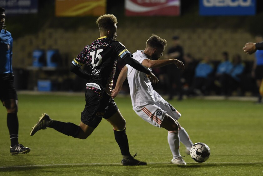 San Diego Loyal's Charles Adams (right) shoots and scores past Las Vegas Lights' Grant Robinson during the first half of USL Championship game Saturday at USD's Torero Stadium.