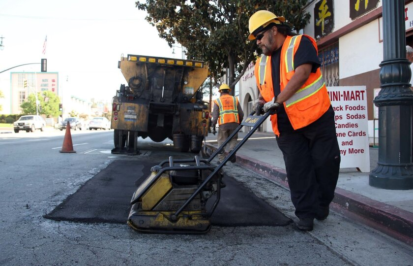 Los Angeles city worker Ralph Mendoza repairs a street in downtown Los Angeles on Thursday, Sept. 11, 2014. Poorly maintained highways and major roads cost Californians an extra $44 billion each year in repairs, accidents and time and fuel burned in traffic, according to a report issued Thursday by a transportation advocacy group. (AP Photo/Nick Ut)