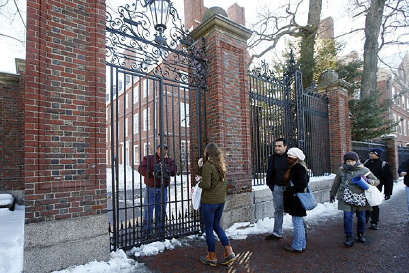 A security officer speaks to students at the entrance to Harvard Yard this week.