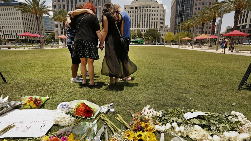 Friends of Shane Tomlinson, who was killed in the Pulse nightclub shooting, gather in prayer and remembrances in downtown Orlando on Monday.