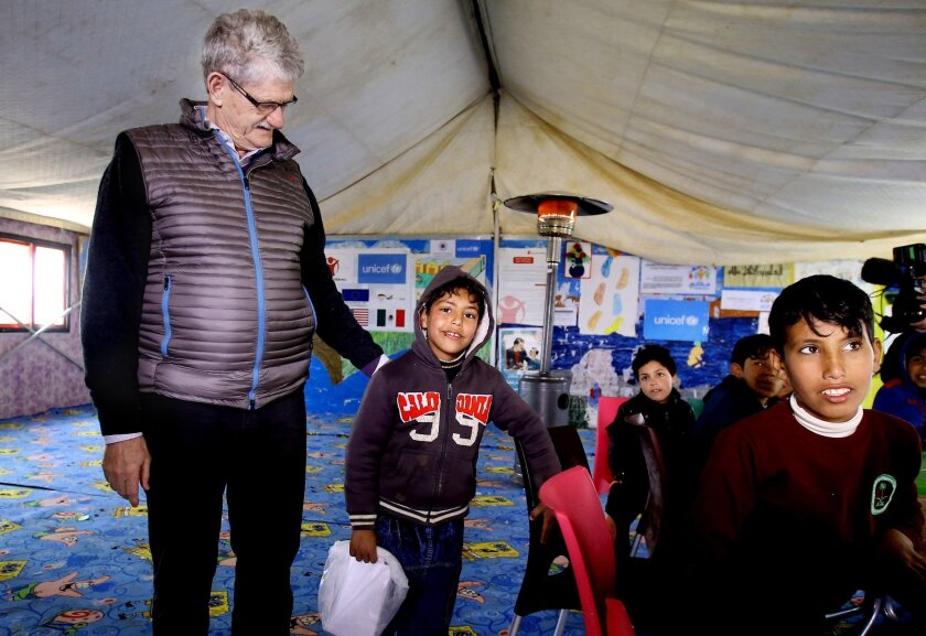 """UN General Assembly President Mogens Lykketoft, left, speaks to a SYrian refugee boy during his visit to Zaatari refugee camp in Mafraq, Jordan, Wednesday, Jan. 20, 2016. Lykketoft visited Zaatari refugee camp in northern Jordan on Wednesday to """"get better knowledge of the size of the problems"""" there, as Syria's five-year-old civil war drags on. Lykketoft is also scheduled to meet with Jordan's King Abdullah II and other Jordanian officials during his stay. (AP Photo/Raad Adayleh)"""