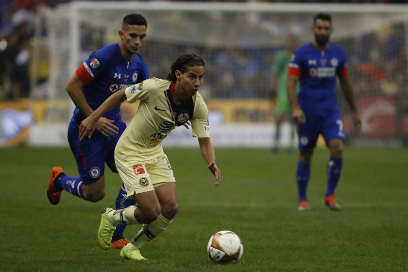 America's Diego Lainez, front, goes for the ball against Cruz Azul during the Mexico soccer league final match at Azteca stadium in Mexico City, Sunday, Dec. 16, 2018.