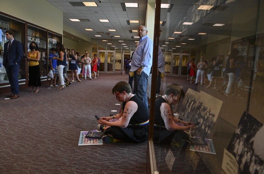People wait in line to speak in person at the Loudoun County school board meting on August 10, 2021 in Ashburn, Va.