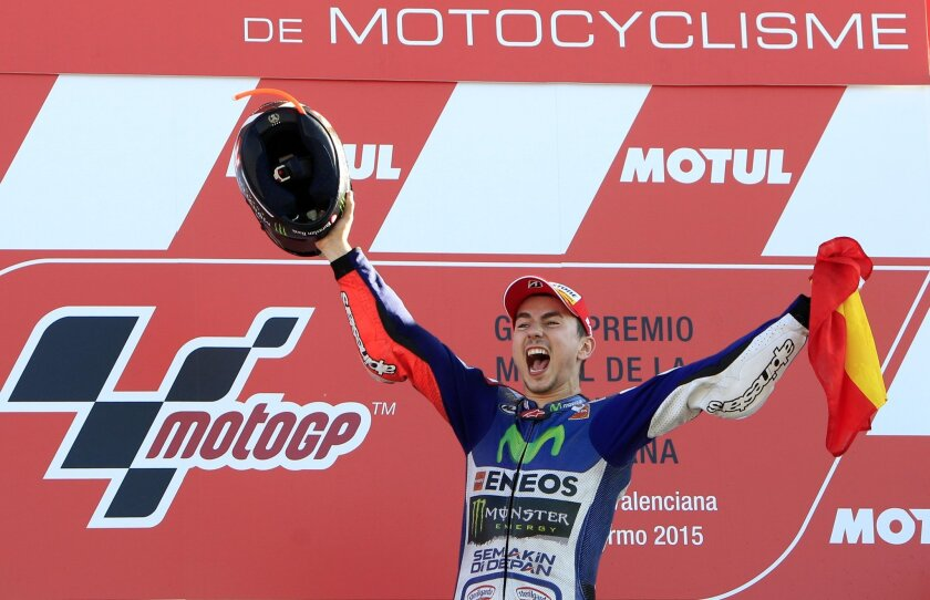 MotoGP rider Jorge Lorenzo of Spain celebrates on the podium after winning the race during the Valencia Motorcycle Grand Prix, the last race of the season, at the Ricardo Tormo circuit in Cheste near Valencia, Spain, Sunday, Nov. 8, 2015. (AP Photo/Alberto Saiz)
