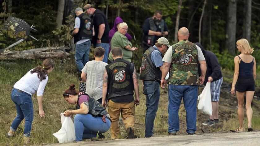 People recover personal items from the scene of a fatal accident on Route 2 in Randolph, N.H., Satur