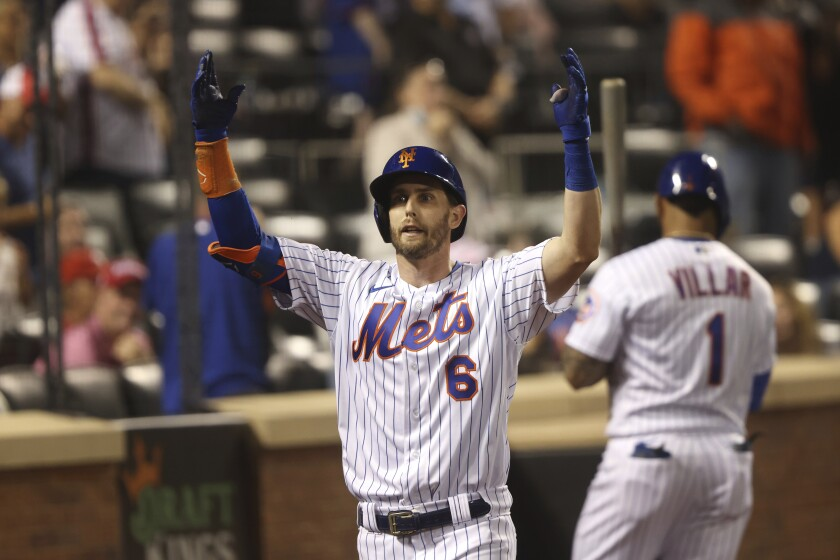 New York Mets' Jeff McNeil celebrates as he returns to the dugout after hitting a home run during the seventh inning of a baseball game against the Philadelphia Phillies, Sunday, Sept. 19, 2021, in New York. (AP Photo/Jason DeCrow)