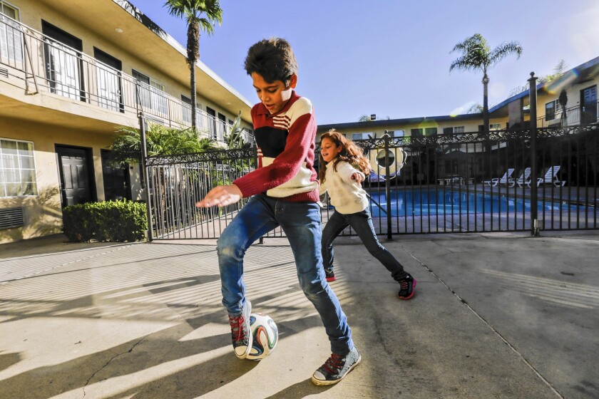 Syrian refugees Omran and Maram Wawieh, 11 and 8, play in the courtyard of the Pomona motel where their family is staying.