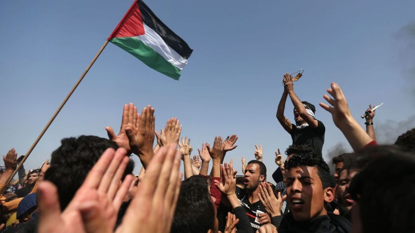 Palestinian demonstrators wave their national flag and shouts slogans against the Israeli security forces during a protest on the Israel-Gaza border on April 6.