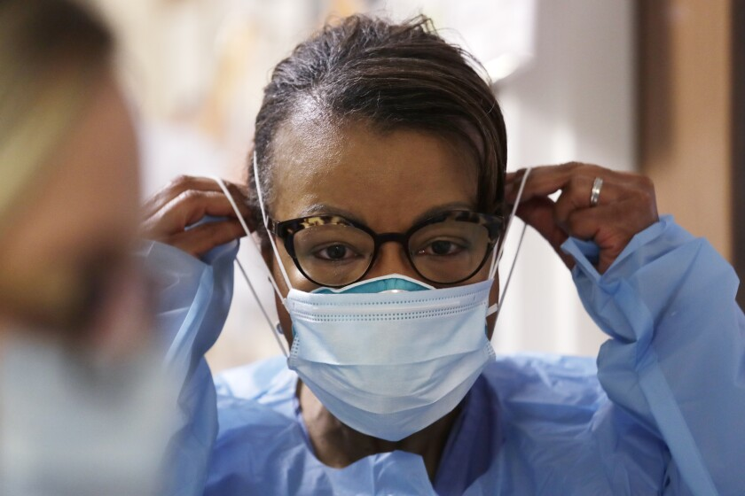 In this Friday, May 8, 2020 file photo, a respiratory therapist pulls on a second mask over her N95 mask.