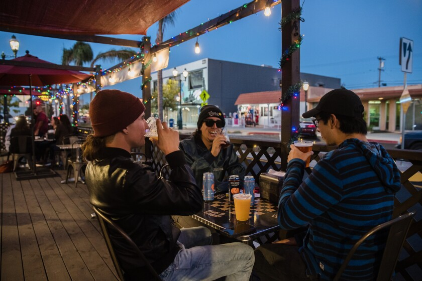 Xavier Sanchez (left), Elliott Osborn (second to left) and Ivan Agundez (right) have drinks outside at Tavern at the Vogue