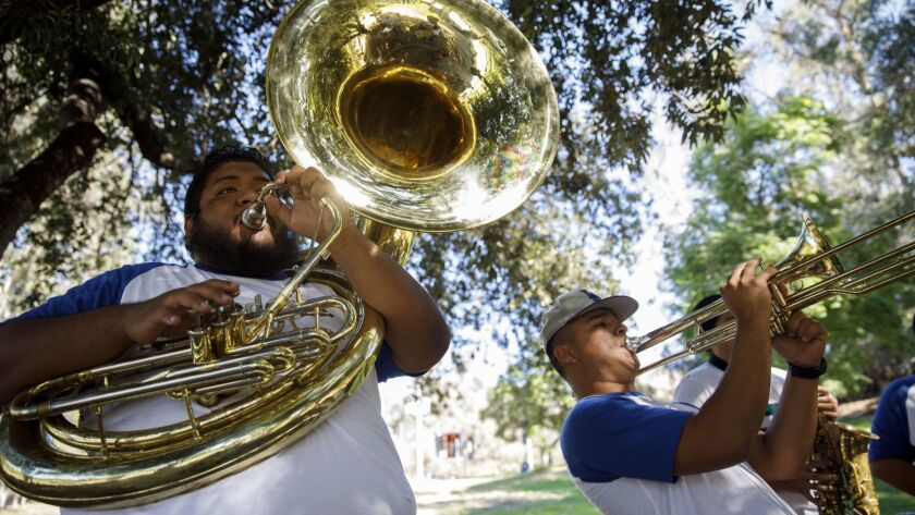 Members of Tamborazo Aguila Y Serpiente play instruments in Elysian Park before Game 3 of the World