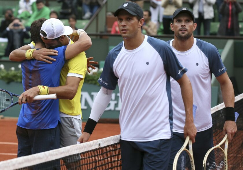 Spanish pair Feliciano Lopez, second left, and Marc Lopez celebrate their victory after winning the men's doubles final match of the French Open tennis tournament against Bob, right, and Mike Bryan, of the U.S,  at the Roland Garros stadium, Saturday, June 4, 2016 in Paris.  (AP Photo/David Vincent