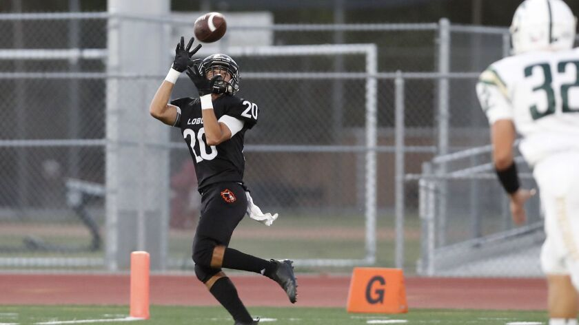 Los Amigos High's Adolfo Chavez completes this reception for a touchdown against Saddleback during t