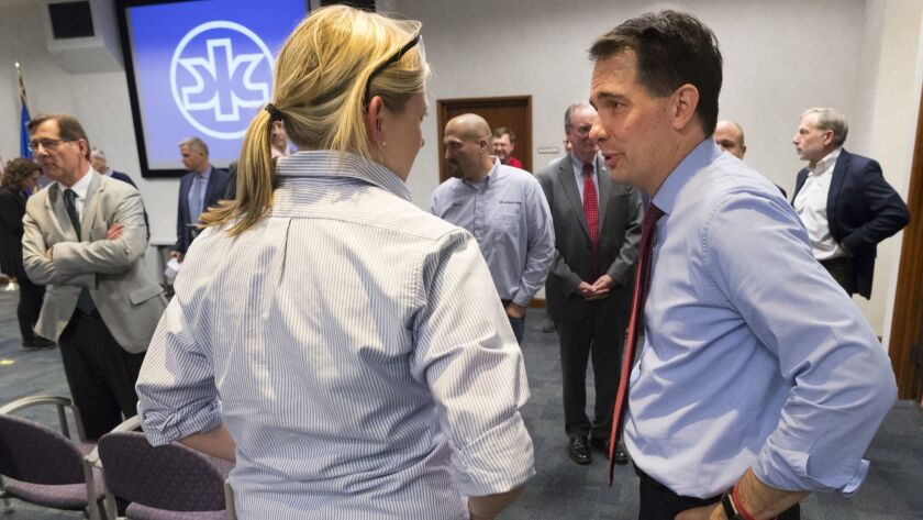 Gov. Scott Walker, right, speaks to a worker at a Kimberly-Clark plant in Neenah, Wis., on Thursday.