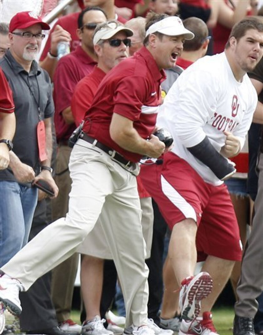 Oklahoma head coach Bob Stoops celebrates an interception off Texas during the first half of an NCAA college football game at the Cotton Bowl in Dallas, Saturday, Oct. 8, 2011. (AP Photo/Mike Fuentes)ab
