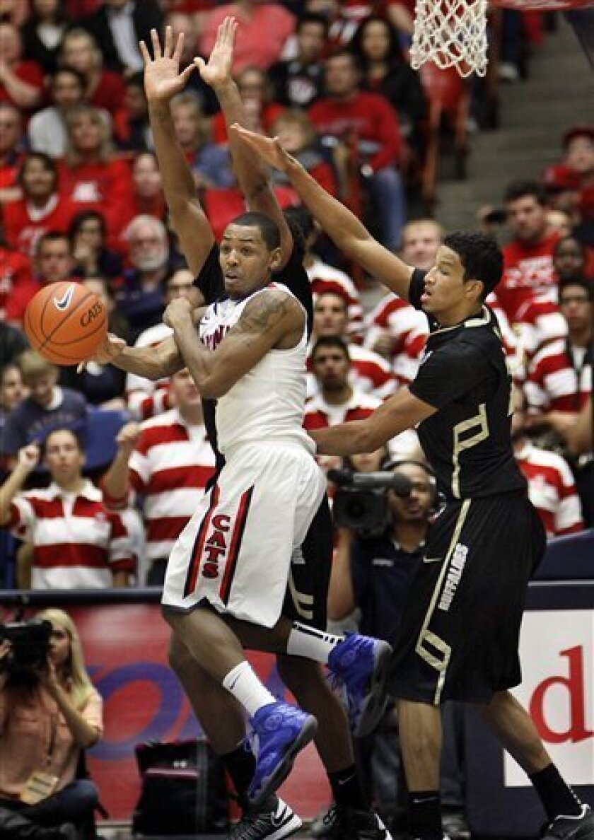 Arizona's Mark Lyons, center, pass the ball against Colorado's Andre Roberson, right, and Xavier Johnson, rear, during the first half of an NCAA college basketball game at McKale Center in Tucson, Ariz., Thursday, Jan. 3, 2013. (AP Photo/Wily Low)