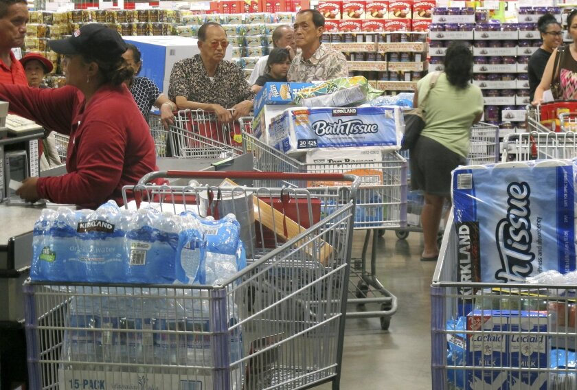 Shoppers stock up on cases of bottled water and other supplies in preparation for a hurricane and tropical storm heading toward Hawaii at the Iwilei Costco in Honolulu on Tuesday, Aug. 5, 2014. Two big storms so close together is rare in the eastern Pacific, and Hurricane Iselle could make landfall by Friday and Tropical Storm Julio could hit two or three days later, weather officials said. (AP Photo/Audrey McAvoy)