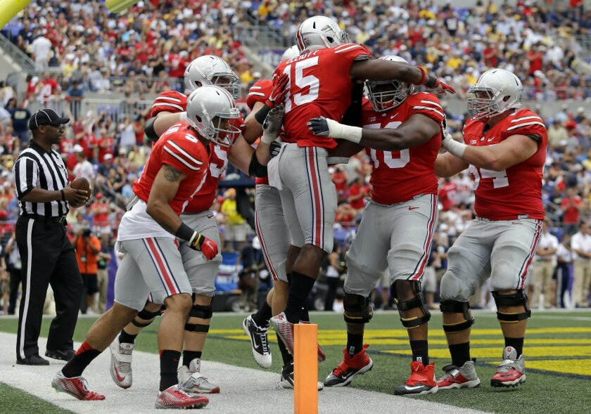 Ohio State running back Ezekiel Elliott (15) celebrates his touchdown with teammates in the second half of an NCAA college football game against Navy in Baltimore, Saturday, Aug. 30, 2014. Ohio State won 34-17. (AP Photo/Patrick Semansky)