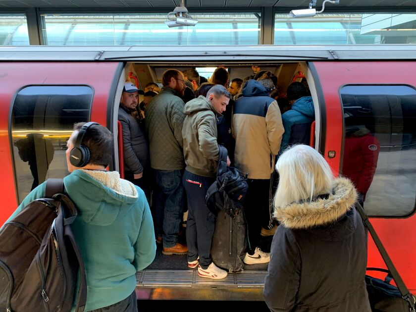 Passengers squeeze onto a busy train at Stratford station in London on March 23, 2020.