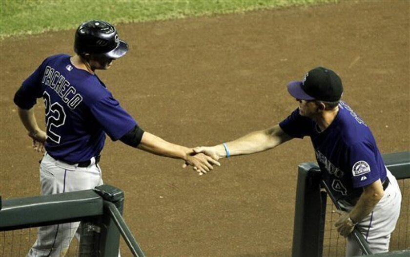 Colorado Rockies' Jordan Pacheco, left, shakes hands with manager Jim Tracy after scoring a run against the Arizona Diamondbacks during the fourth inning of a baseball game on Wednesday, Oct. 3, 2012, in Phoenix. (AP Photo/Ross D. Franklin)