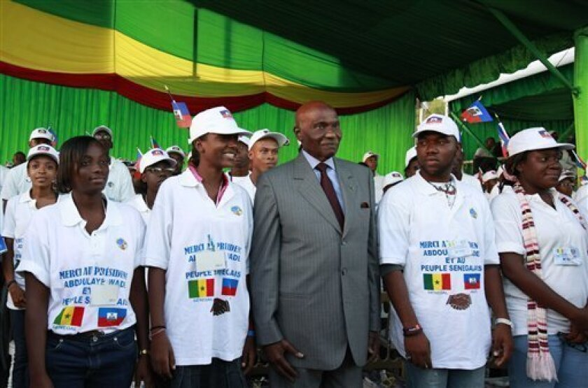 Senegalese President Abdoulaye Wade, second right, poses for a picture with Haitian students, wearing tee-shirts reading 'Thank you President Wade' at a ceremony welcoming the students to Dakar, Senegal Wednesday, Oct. 13, 2010. Senegal is one of the poorest countries in the world and its GDP is on