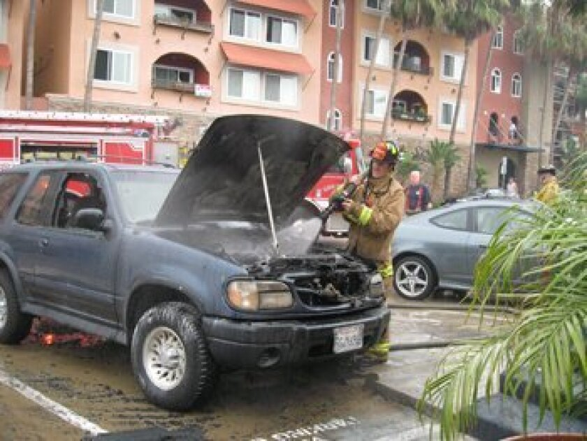 Firefighters extinguish an engine fire in a Ford Explorer in Pacific Beach. Photo: Lorri Sabban