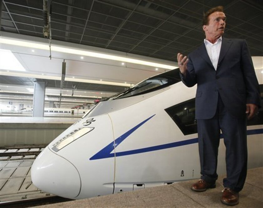 California Gov. Arnold Schwarzenegger speaks next to a China's high-speed train at Hongqiao Railway Station in Shanghai, China, Sunday, Sept. 12, 2010. Schwarzenegger is riding the rails, China's new high speed train lines, engaging in a little window shopping while peddling Californian exports and