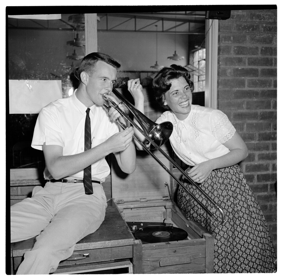 A young white man plays the trombone while a young white woman sitting next to him snaps her fingers.