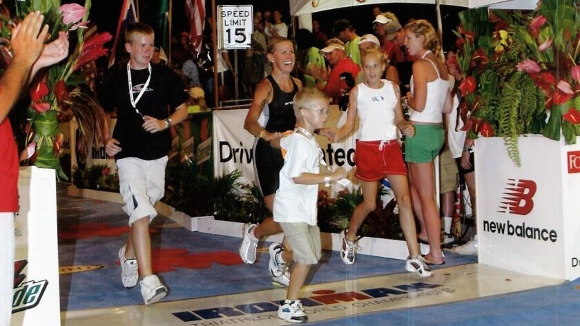 Kathleen McCartney crosses the finish line of the 2003 Ironman with her kids.