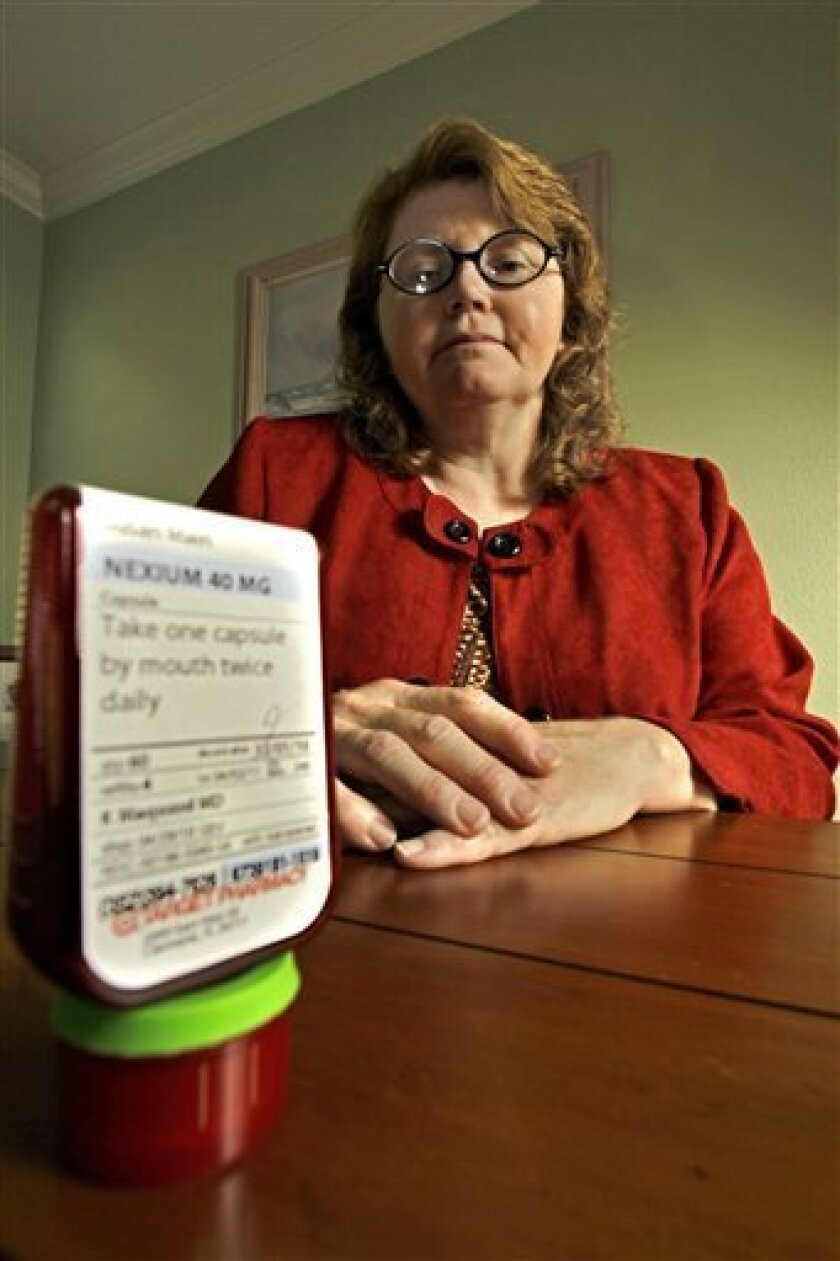 In this May 23, 2010 photo, Susan Main sits near her medicine for acid-reflex in Minneola, Fla. She was forced to give up her usual acid-reflex drug that was covered under her old insurance plan when she switched to her husband's health plan, and she now has to use a less-effective drug. (AP Photo/John Raoux)
