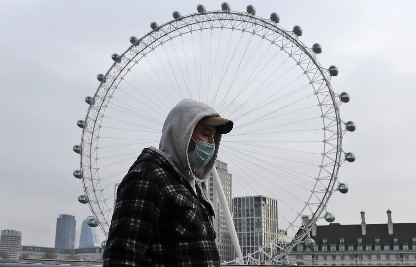 A man wearing a face covering walks past the London Eye in London